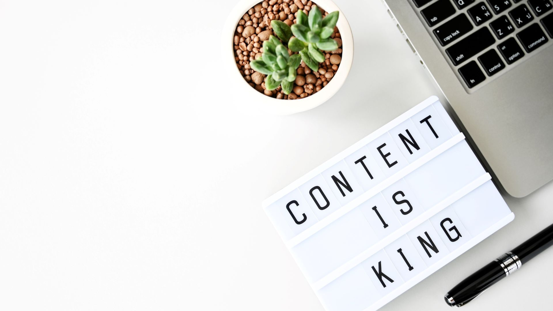 Content marketing workstation with laptop and sign saying 'content is king'