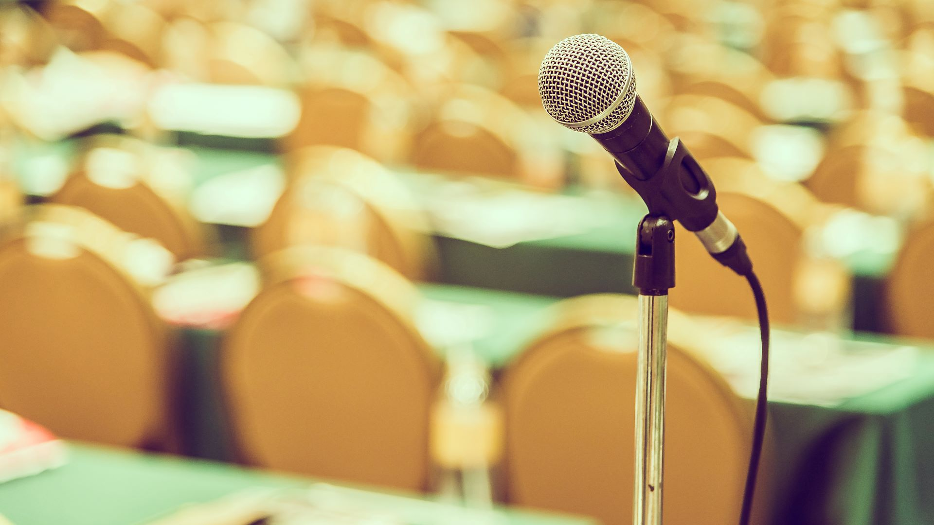 Microphone and conference room at Cruise Planners franchise convention