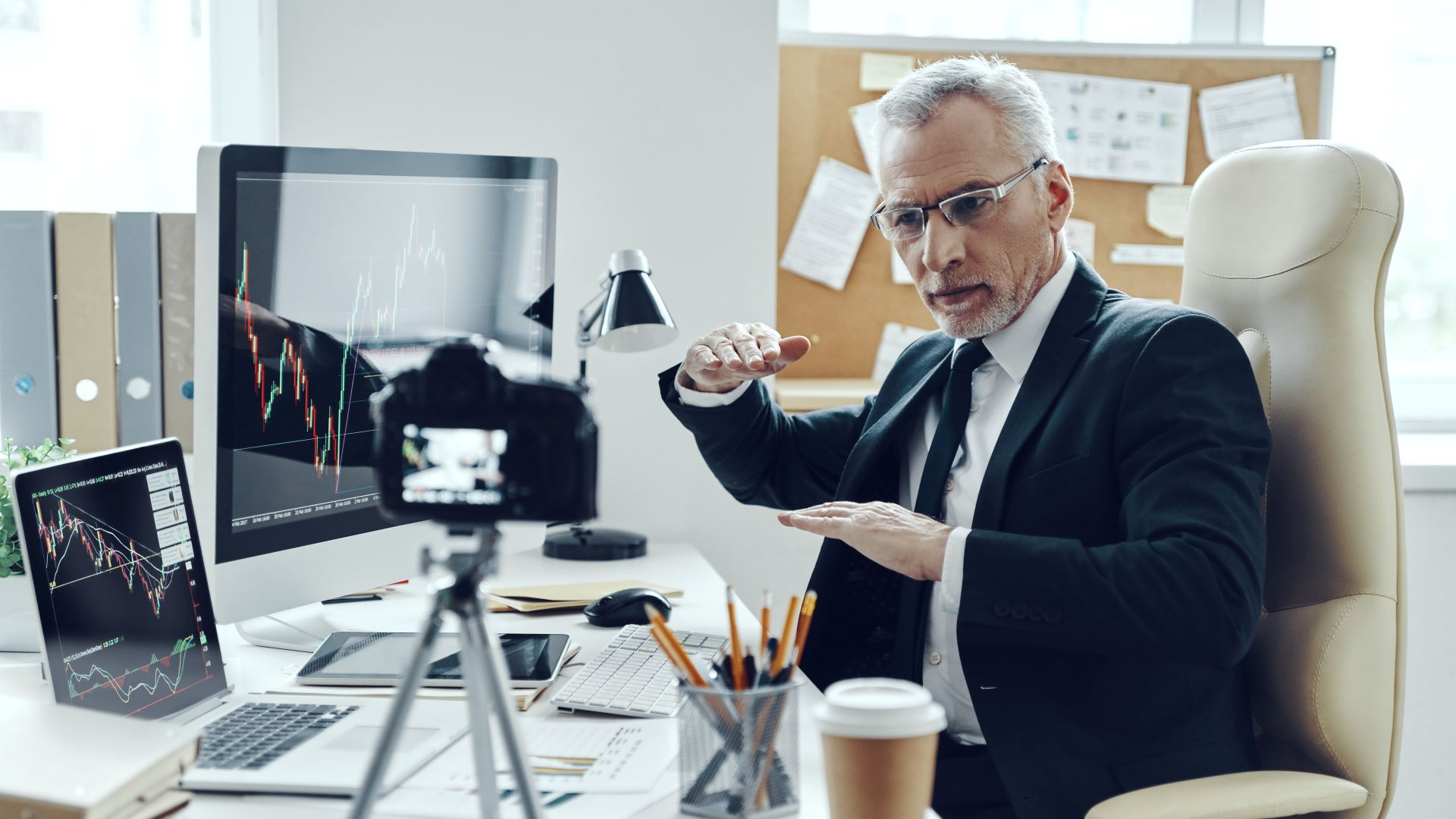 Businessman filming a killer corporate video in his office