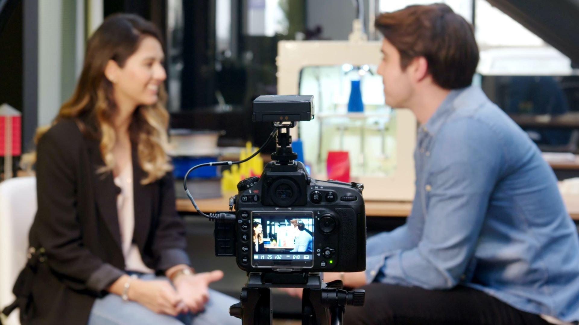 Video director preparing onscreen talent for a shoot behind a camera