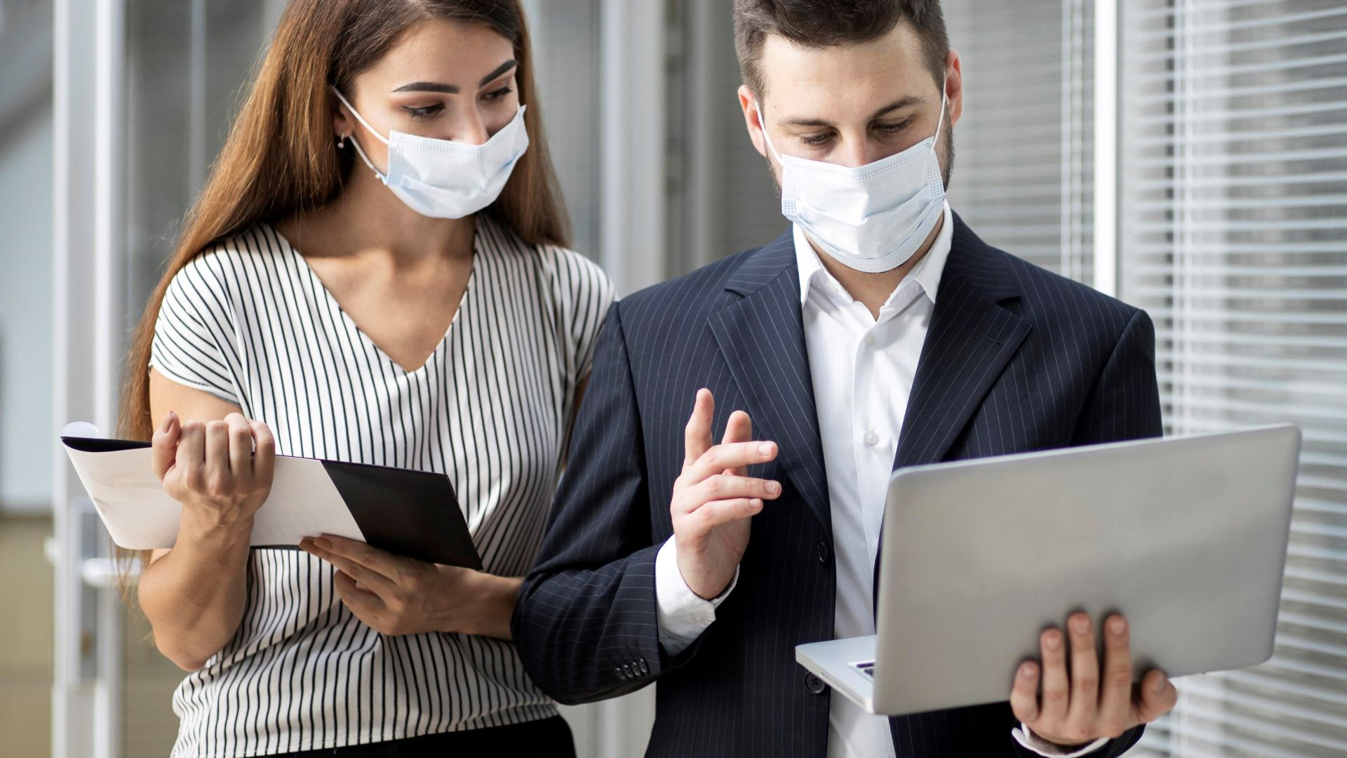Colleagues watching a company video during COVID-19 wearing surgical masks