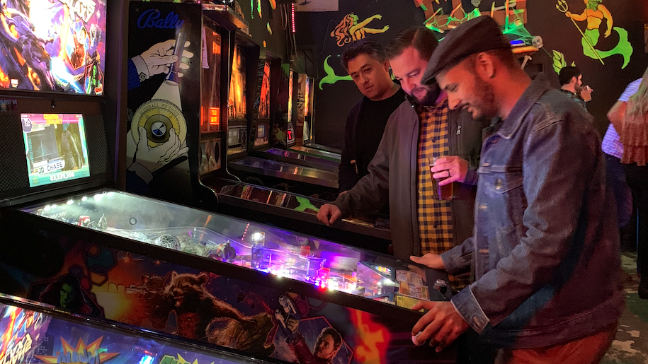 Marketing agency partners strategizing new vision over a pinball machine